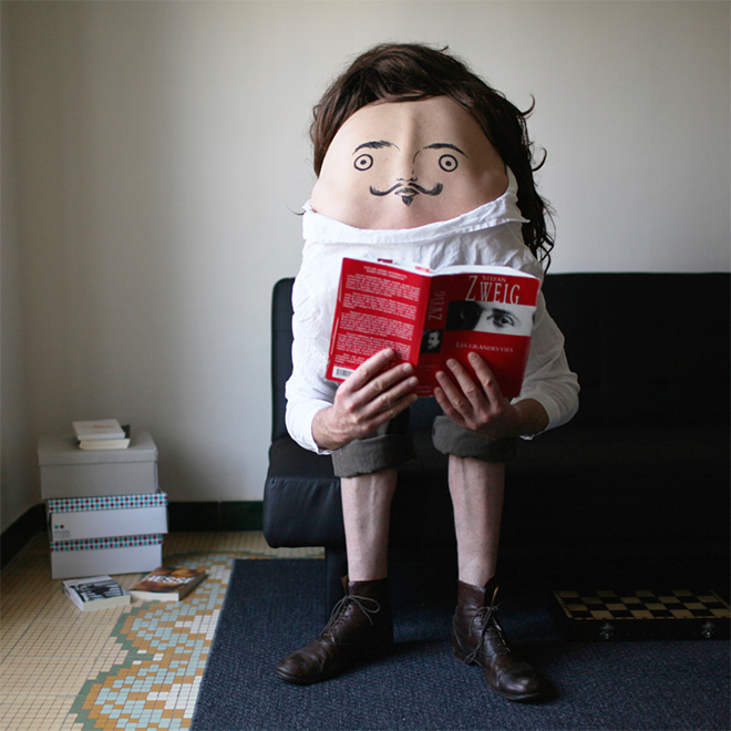 Creepy body art creature reading a book.
