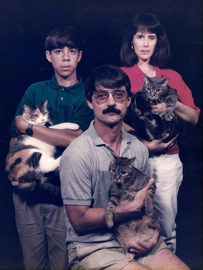 Awkward family posing with a cat.